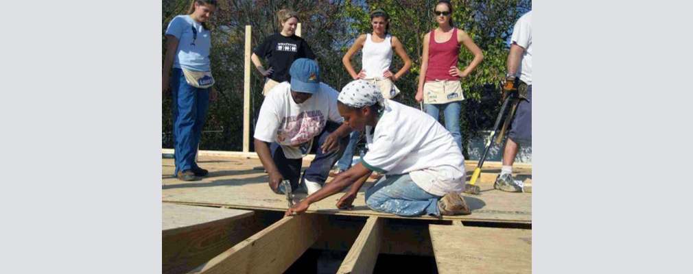 Photograph of seven volunteers laying plywood for the subfloor of a house.