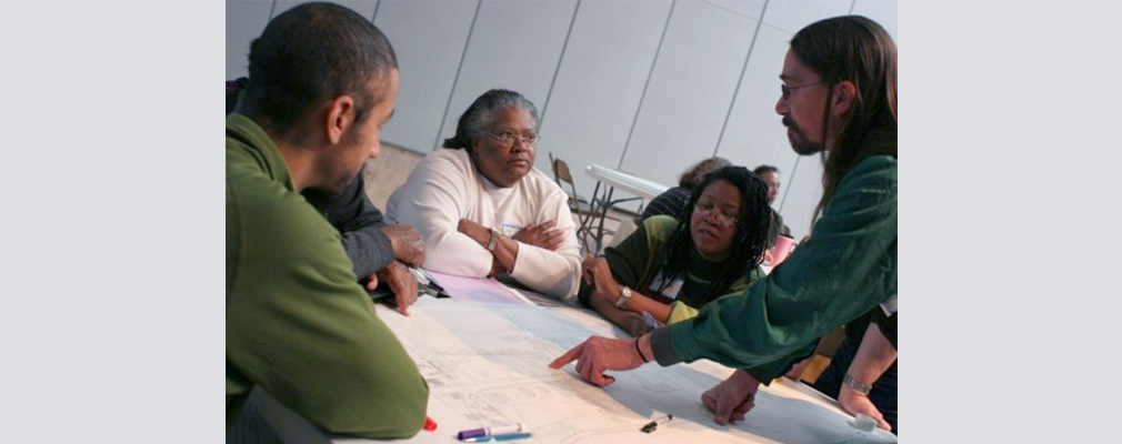 Photograph of five people discussing plans laid out on a table inside a large meeting room.