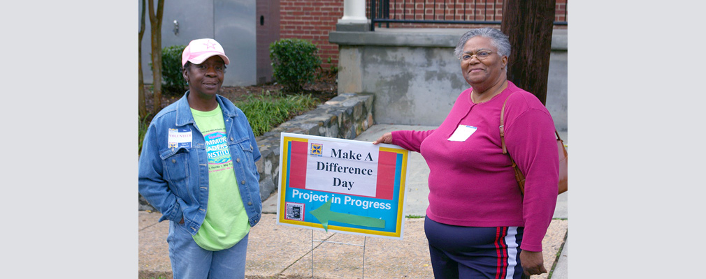 "Photograph of two adults standing beside a sign reading ""Make A Difference Day. Project in Progress."""