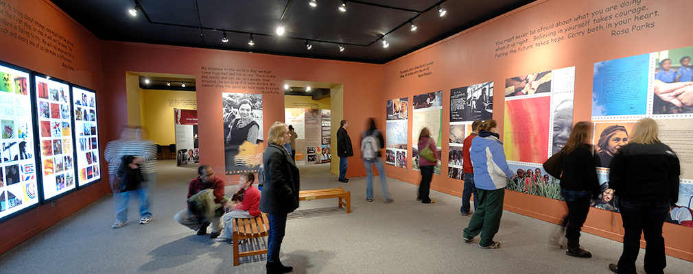Interior photograph of people looking at an exhibition.
