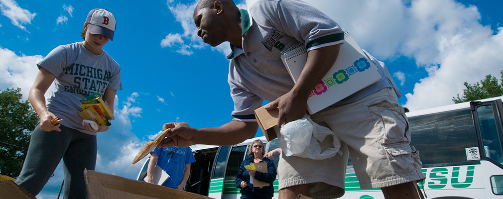 Photograph of two university students sorting school supplies in front of an MSU bus.