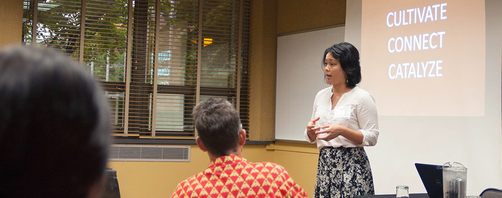 A woman gives a presentation at the front of a classroom.