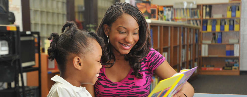 Photograph of a female college student tutoring a young girl as she reads a book in the school library.