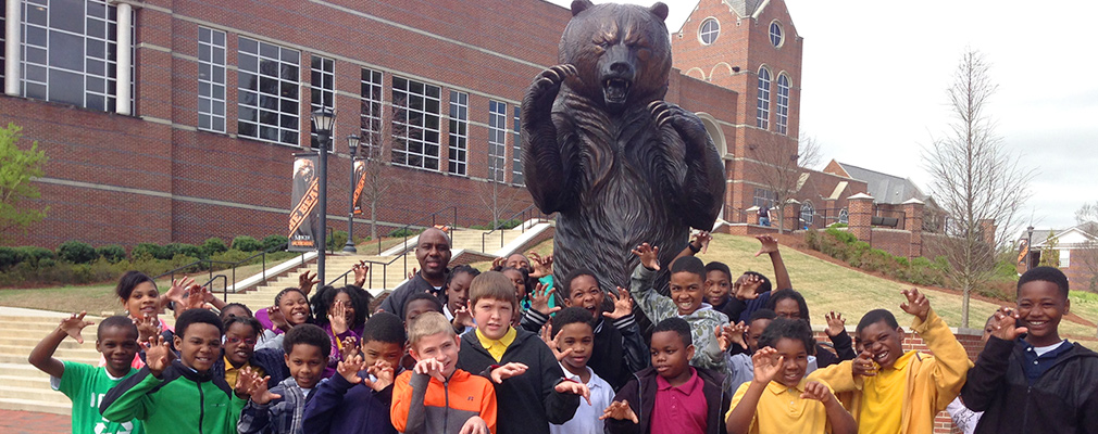Photograph of approximately 30 elementary school students and a teacher in front of a statue of a bear, the university's mascot.