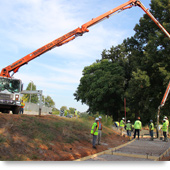 A photograph shows a truck pouring concrete to form the path along a portion of the Westside Trail.