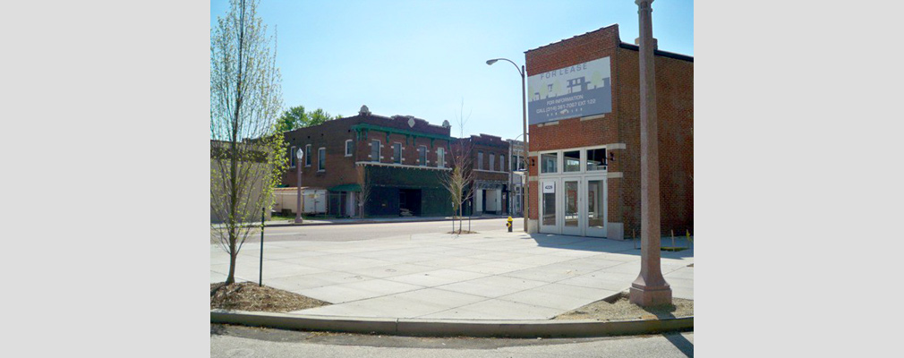 Photograph of a paved plaza with newly planted trees in front of a two-story brick commercial building, with similar buildings in the background across the street.