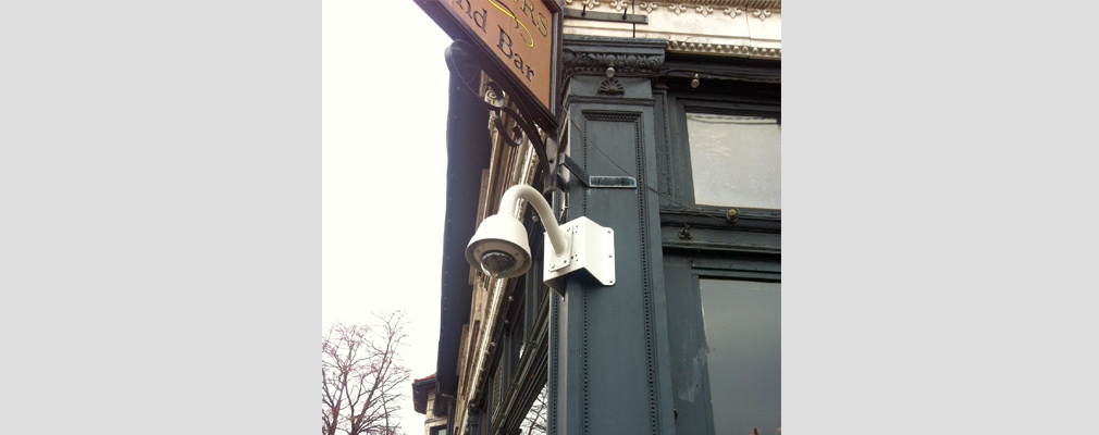 Photograph of a security camera affixed to the corner of a commercial building.