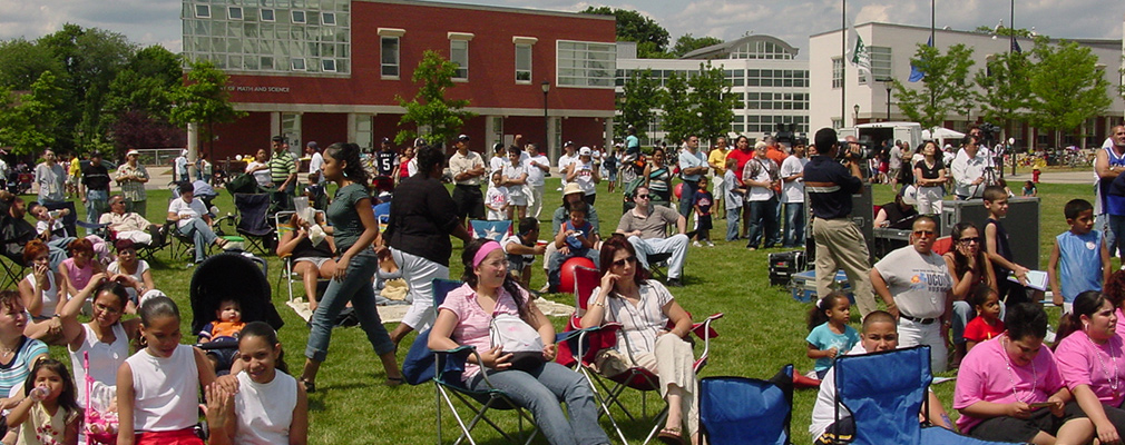 Photograph of a large crowd sitting on the lawn of the Learning Corridor during a community.