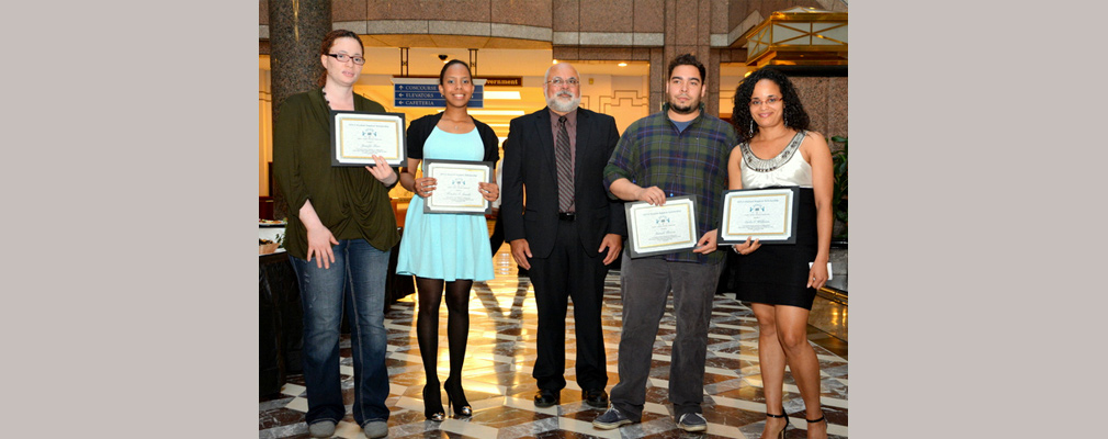 Photograph of four scholarship winners standing with SINA's executive director, Melvyn Colón.