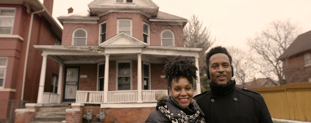 Photograph of a man and a woman standing in front of a two-story brick single-family house.