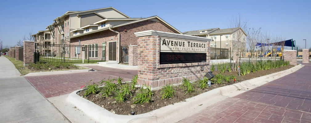 Photograph of the entrance to Avenue Terrace, with a brick monument sign in the street median in the foreground, a one-story community building and playground in the middleground, and three-story multifamily buildings in the background.