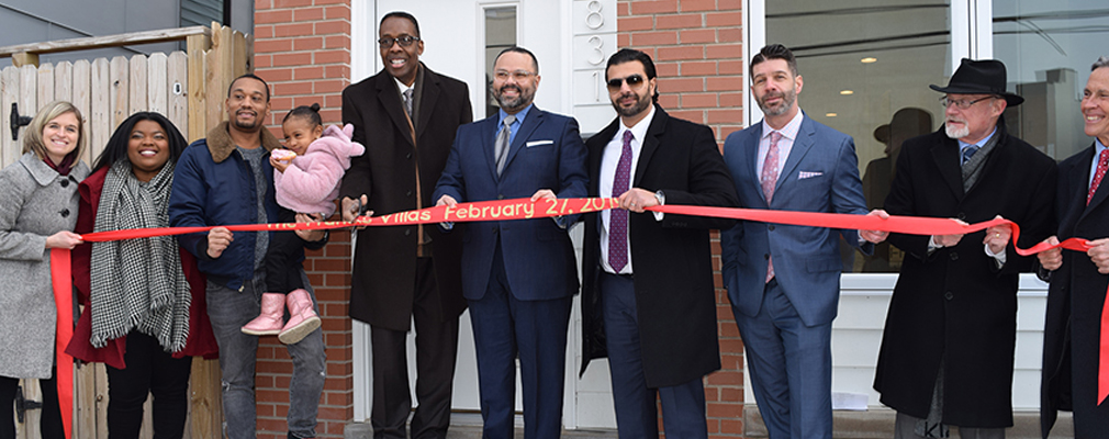 Photograph of developers, city officials, and new residents at the Francis Villas ribbon cutting in 2019.