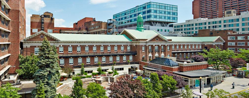 Photograph taken several stories above street level of the Moses medical campus, a cluster of modern and historic buildings around a central, tree-lined courtyard.