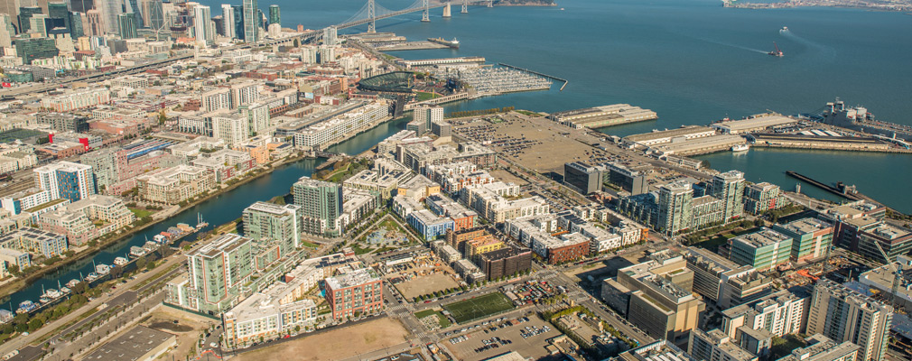 Low-angle aerial photograph of a waterfront neighborhood in San Francisco, with the Financial District and Oakland Bay Bridge in the background.
