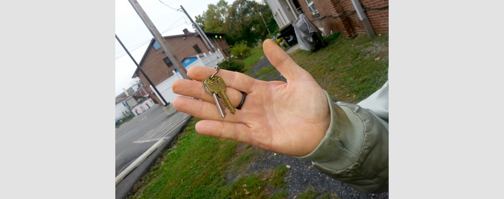 Photograph of a hand holding a set of two house keys.