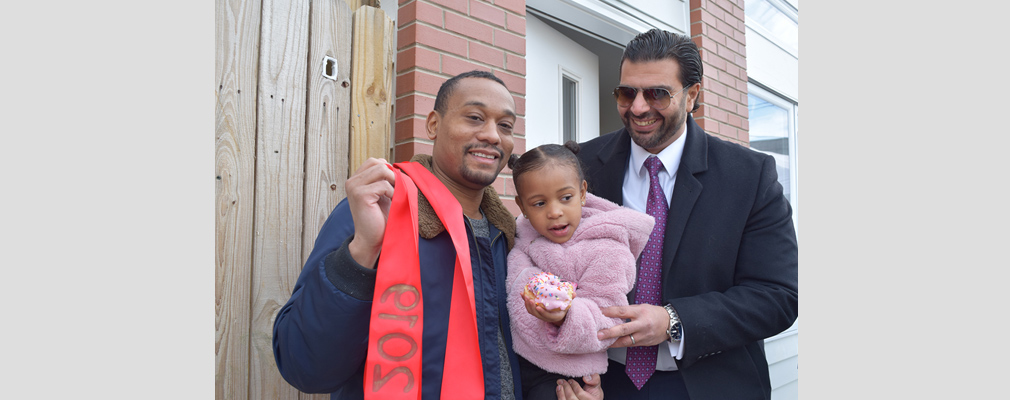 Photograph of a new homeowner and his child with the developer of Francis Villas.