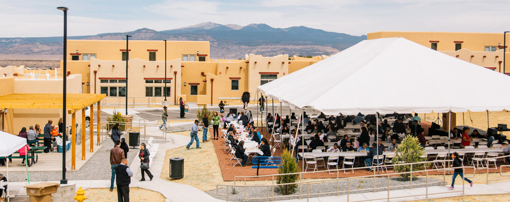 Photograph taken from one story above ground of community members standing near and seated under a large tent during the Cedar Hills' opening ceremony. The single-story community building is at the left edge of the photograph, and a row of attached residential buildings is in the middle ground.