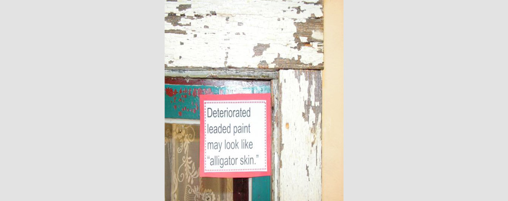"Photograph of chipping paint on a window frame with a sign that reads ""Deteriorated leaded paint may look like 'alligator skin.'"""