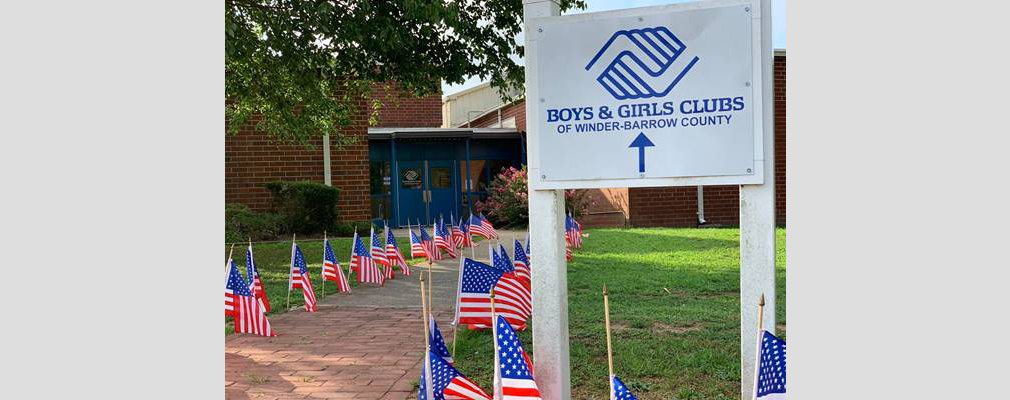 Photograph of a sidewalk leading to a doorway lined with American flags and marked with a sign containing the logo of the Boys & Girls Clubs of Winder-Barrow County.