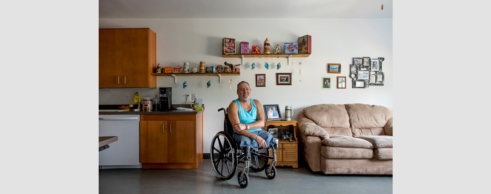 Photograph of a man in a wheelchair in the kitchen-living area of an apartment with various decorations and personal items adorning the wall.