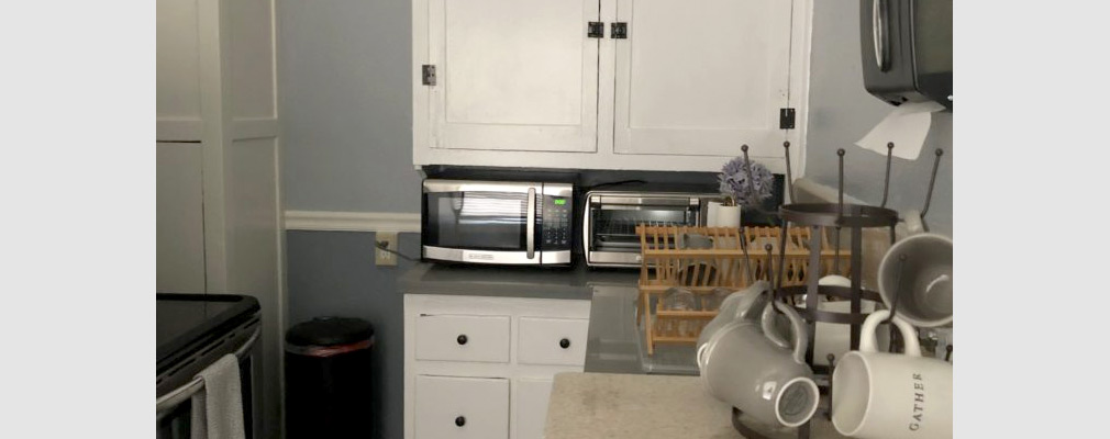 Photograph of a kitchen, with cups, a sink, a microwave, and a toaster oven on a counter between upper and lower cabinets.