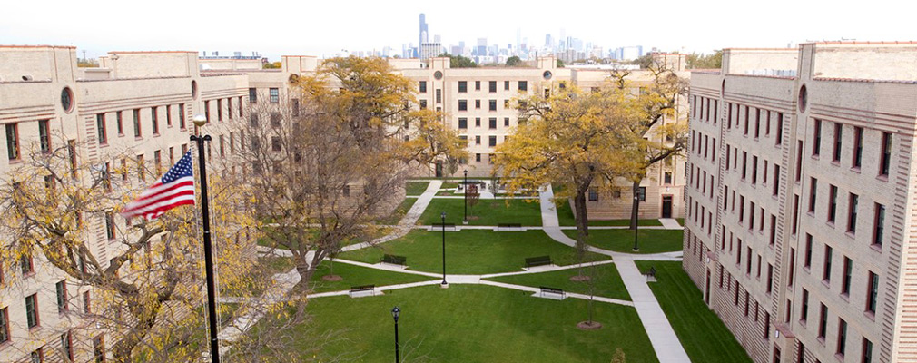 Photograph of the interior courtyard framed by the five-story multifamily building with the downtown Chicago skyline in the background.