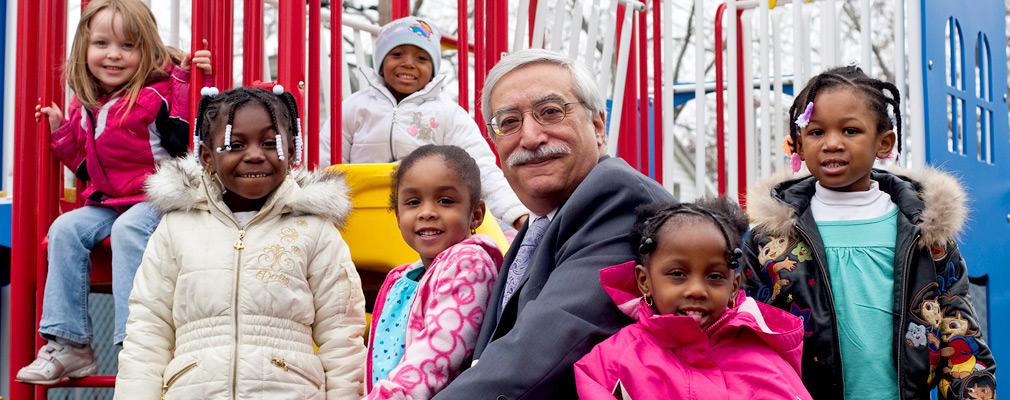 Photograph of six children surrounding a man seated on a piece of playground equipment.