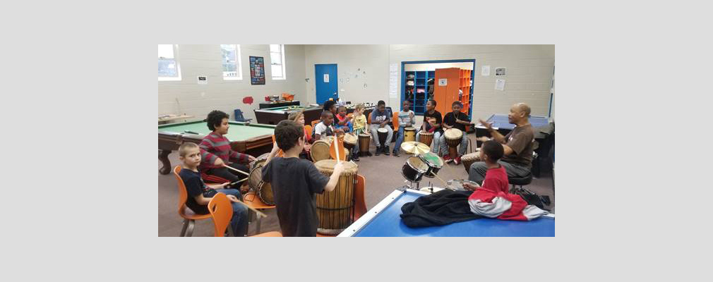 Photograph of a large room with a group of children playing drums and seated in a semicircle  facing an adult instructor.