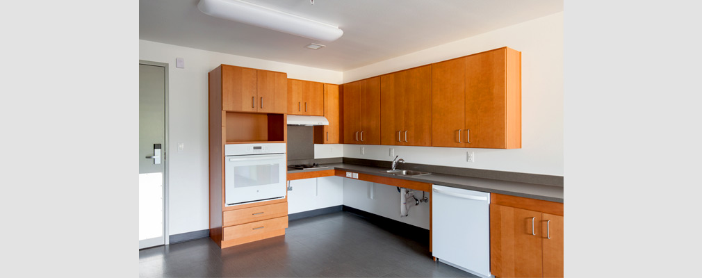 Photograph of a kitchen with an oven, stovetop, sink, dishwasher, roll-under counter space, and cabinets.