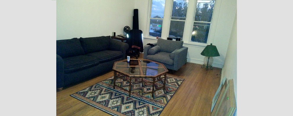 Photograph of a living room, with a table and an upholstered sofa and chair and with large windows on the far wall.