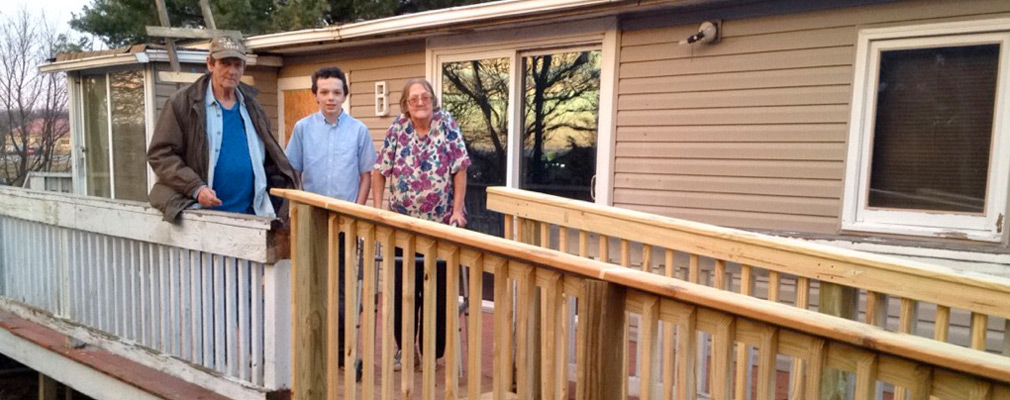 Photograph of three residents standing on their front porch at the top of a newly constructed ramp.