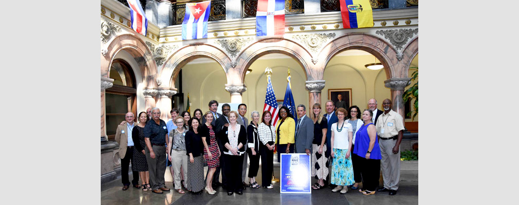 "Photograph of 25 community stakeholders and city officials standing in Rochester's city hall behind a poster that says ""Let's Make Lead History."""