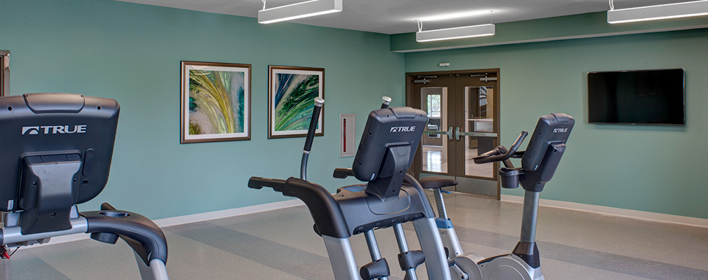 Photograph of a large room with a stationary bike, stair stepper, and treadmill.