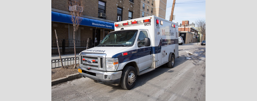Photograph of an ambulance parked on a street, with multistory brick buildings in the background.