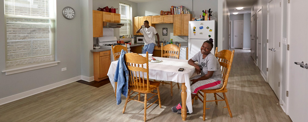 Photograph of two people in an apartment with a large kitchen and dining area and with a wide hallway leading to the rear of the apartment.
