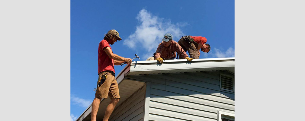 Photograph of three men working on the roof of a house.