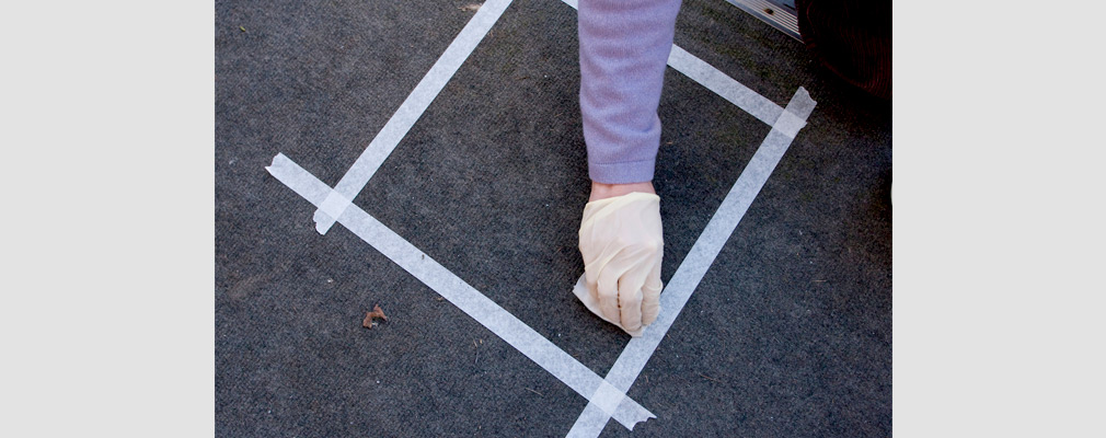 Photograph of a gloved hand wiping a cloth within a taped square on a floor.