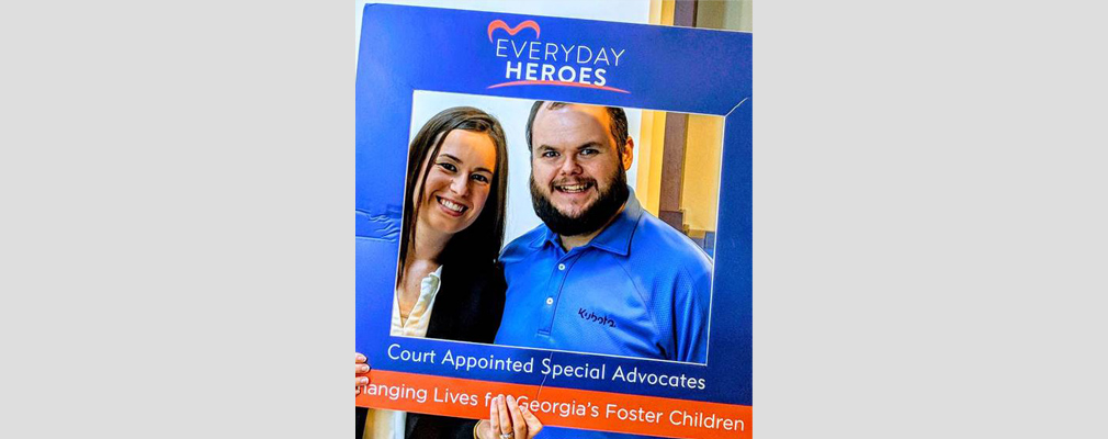 "Photograph of two smiling people posing behind a cardboard frame printed with the text: ""Everyday Heroes,"" ""Court Appointed Special Advocates,"" and ""Changing Lives for Georgia's Foster Children."""