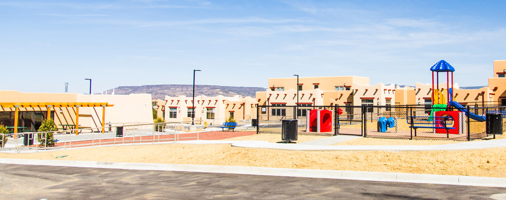 Photograph of the single-story community building (left) and playground (right), with attached residences in the background.