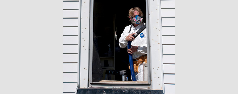 Photograph of a contractor wearing a respirator mask while using a vacuum to clean a window frame.