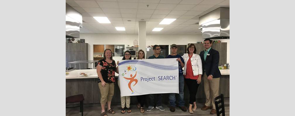 "Photograph of seven people holding up a banner that reads ""Project SEARCH."""