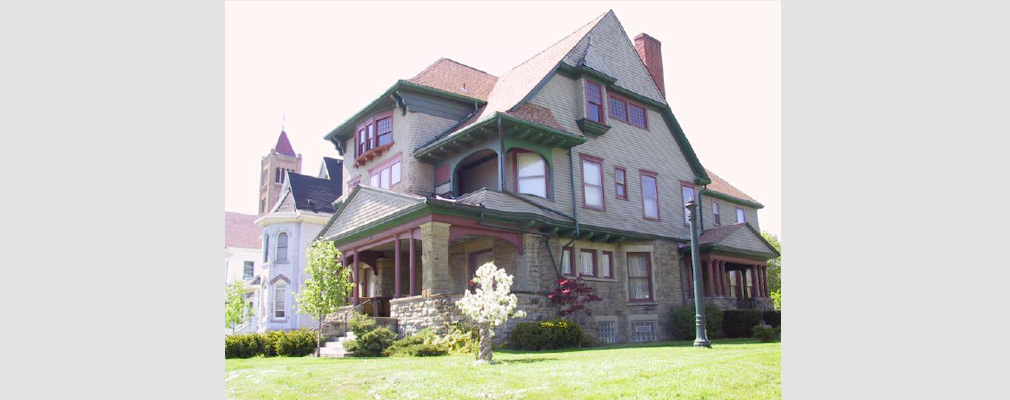 Photograph of two facades of a three-story Victorian style home with a yard in the foreground.