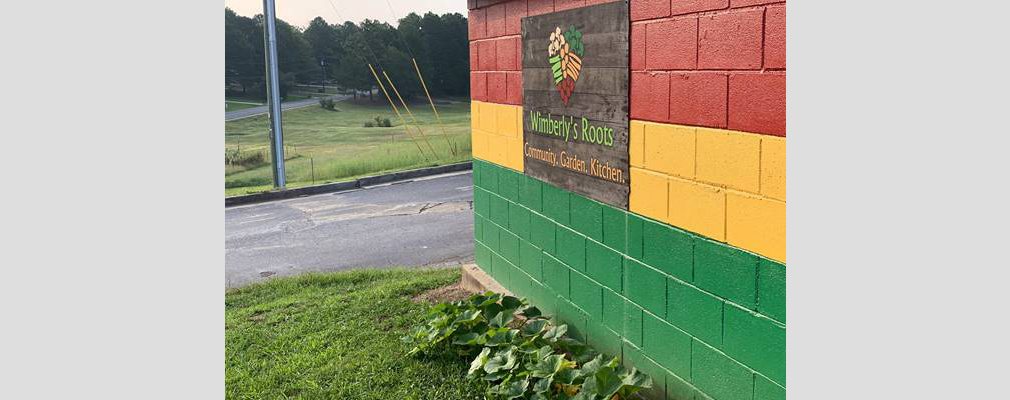 "Photograph of a sign with a black background that reads ""Wimberly's Roots. Community. Garden. Kitchen."" mounted on an exterior wall of a cinder block building painted in the Pan-African colors."