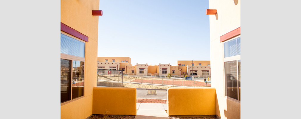 Photograph taken from within a courtyard across the central common space to one- and two-story attached residences in the background.