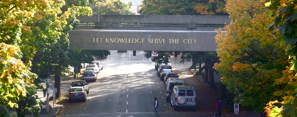 "Photograph of a bridge on the Portland State University campus bearing the motto, ""Let Knowledge Serve the City."""