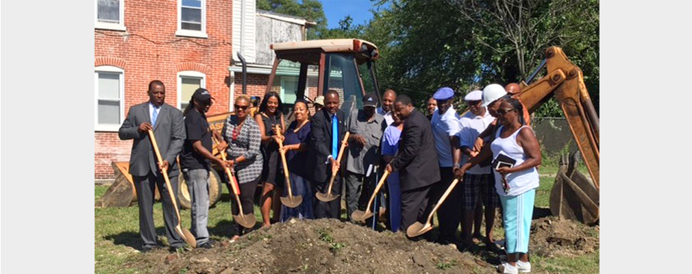 Photograph of 17 people holding shovels as part of a groundbreaking ceremony.