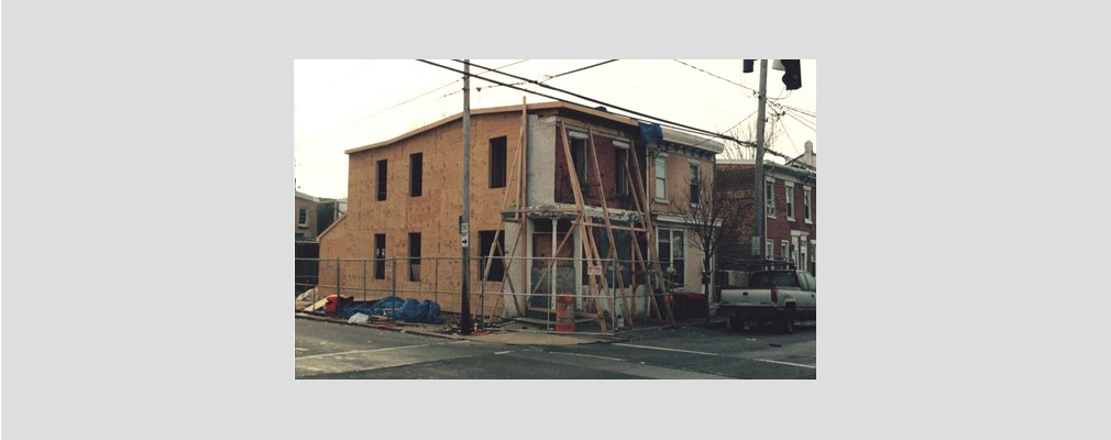 Photograph of a two-story rowhouse under construction on a corner lot.