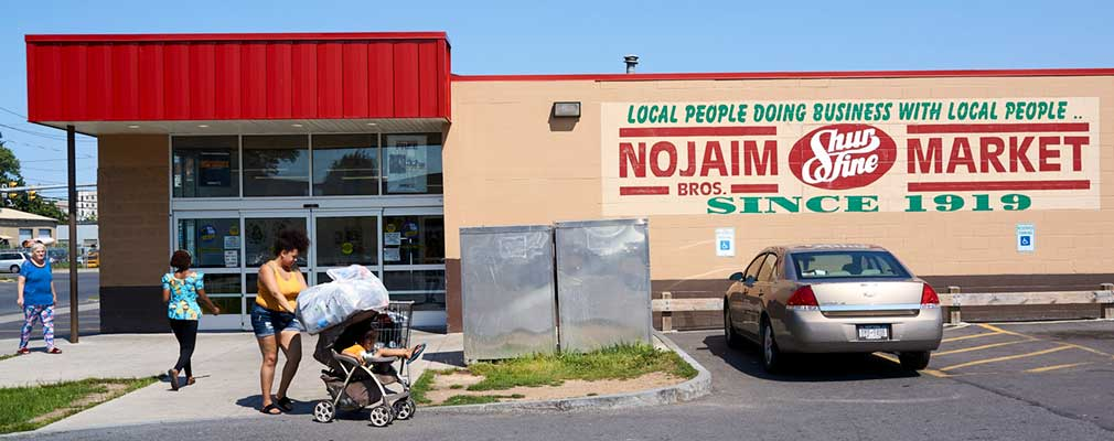 "Photograph of the parking-lot side façade of a one-store grocery building, with a wall sign that says ""Nojaim Bros. Market, since 1919."""