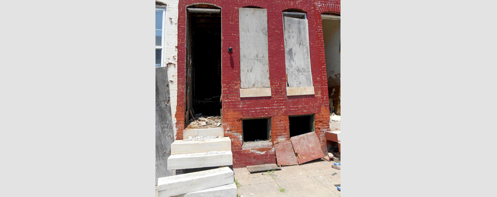 Photograph of the front of a blighted rowhouse with boarded-up windows, an empty doorframe, and debris in the doorway.
