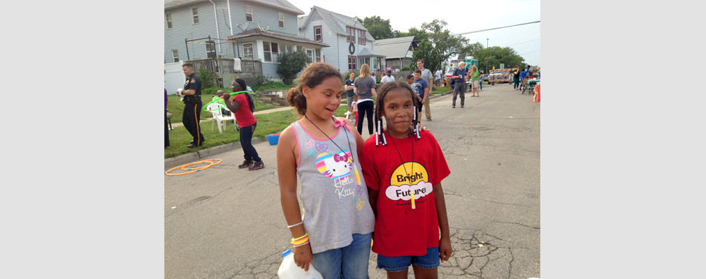 Photograph of two children at a neighborhood block party.